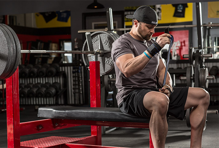 Layne Norton preparing to do a heavy bench press as he puts wrist wraps around his wrists
