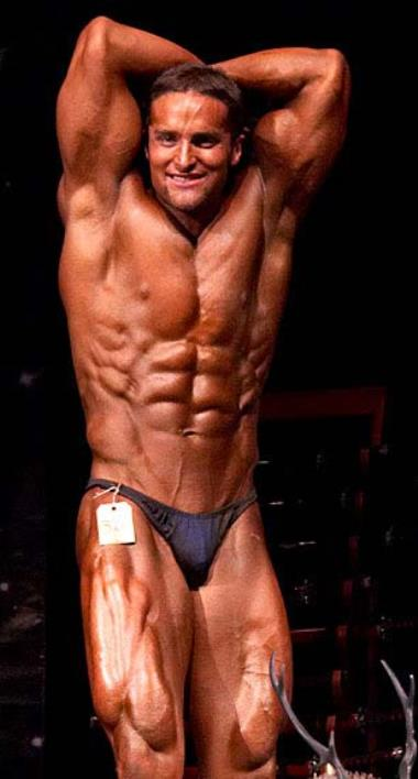 Layne Norton showing his abs to the audience in front of the bodybuilding stage