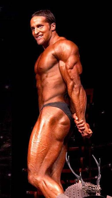 Layne Norton in a side triceps pose on a bodybuilding stage