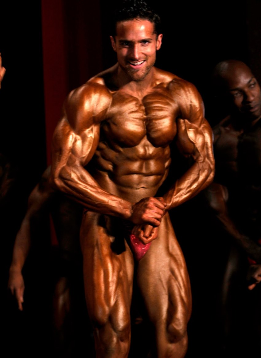 Layne Norton tanned up on a stage, posing alongside other competitors