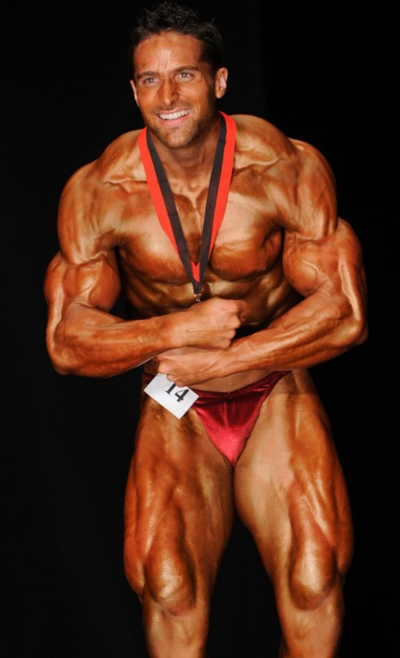 Layne Norton profile picture, where he stands in front of the audience on the bodybuilding stage, in a most muscular pose, with a title-winning medal around his neck