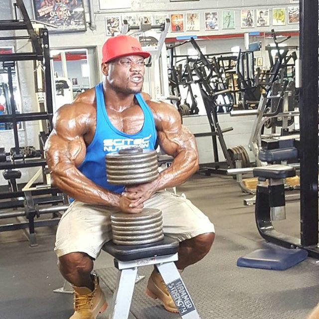maxx charles holding dumbbell at the gym