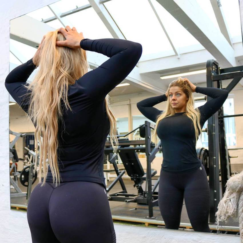 Mia Sand looking at herself in the mirror in the gym while showing her glutes in dark blue leggings