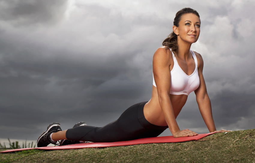 Michelle Bridges doing yoga exercises in the outdoors, lying on a mat