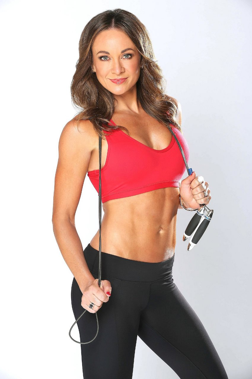 Michelle Bridges profile picture, in which she holds a resistance band, and shows her ripped abs