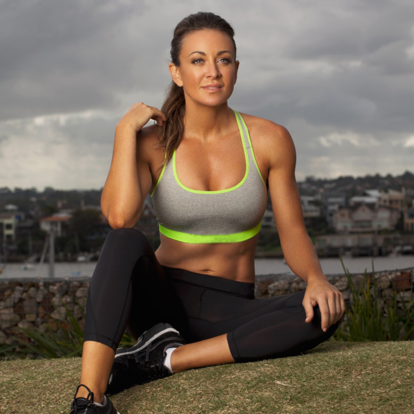 Michelle Bridges sitting on grass, with a village and a river in the background