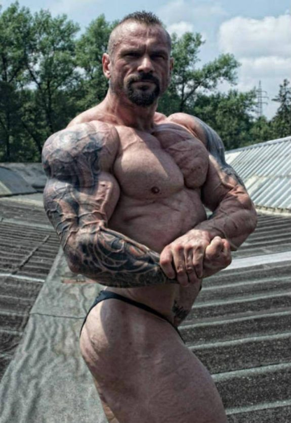 Miha Zupan tensing his bicep while standing outdoors