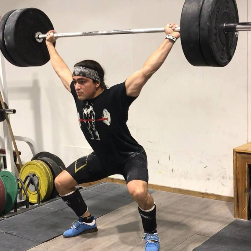 Omar Isuf doing an overhead press exercise with barbell