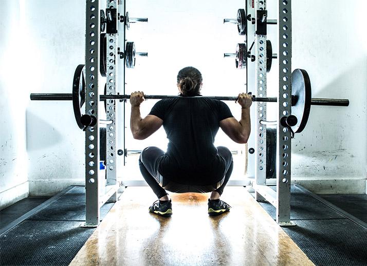 Back shot of Omar Isuf doing squats