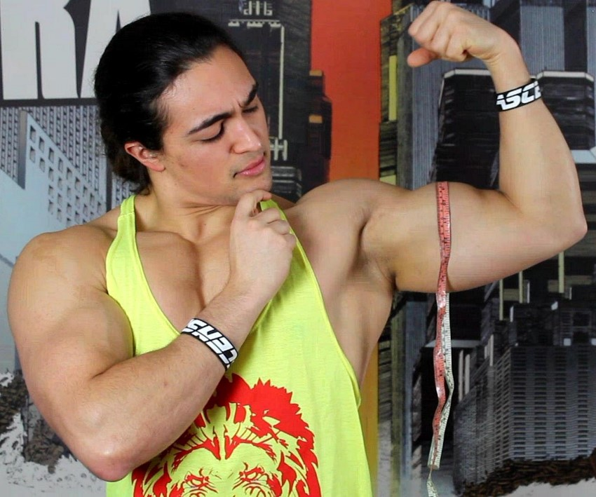 Omar Isuf in a yellow tank top, measuring his flexed biceps
