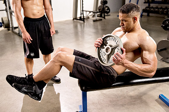 One of the Hodgetwins doing ab twists in a gym, while the other one is looking at him