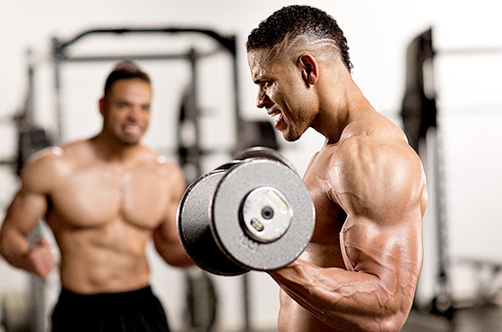One of the Hodgetwins doing biceps curls while the other is motivating him to do more