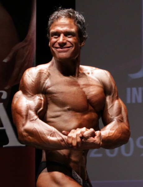 Rob Deluca in a side chest pose while on a stage