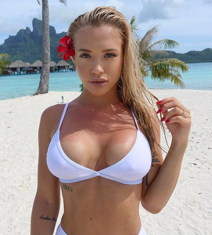 Tammy Hembrow in a white bikini at the beach looking directly into the camera