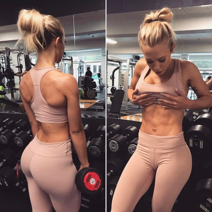 Tammy Hembrow flexing her abs and glutes in front of a gym mirror