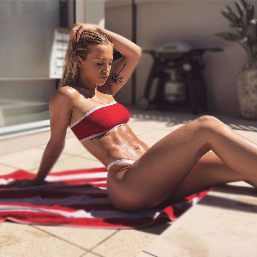 Tammy Hembrow lying in the backyard, tanning her ripped body