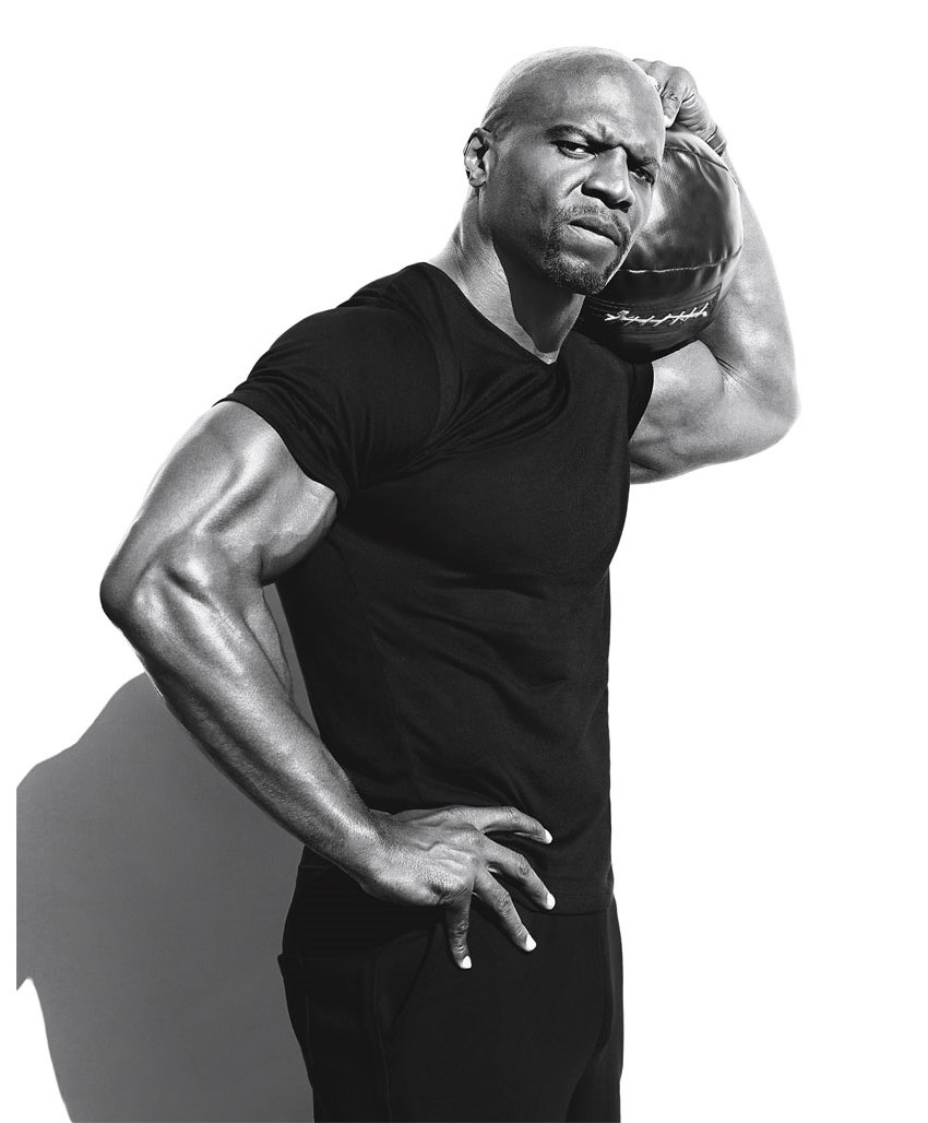 Terry Crews looking seriously in the camera during a photoshoot, meanwhile he's also holding an American Football ball in his arm
