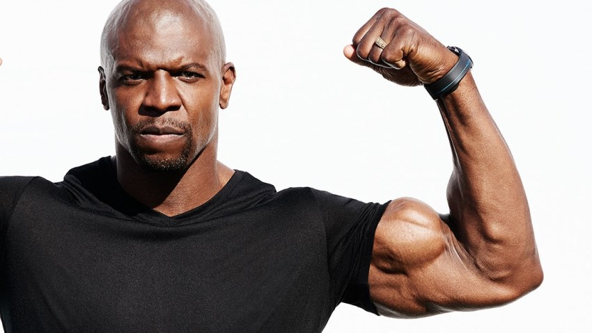 Terry Crews flexing his biceps in a black t-shirt