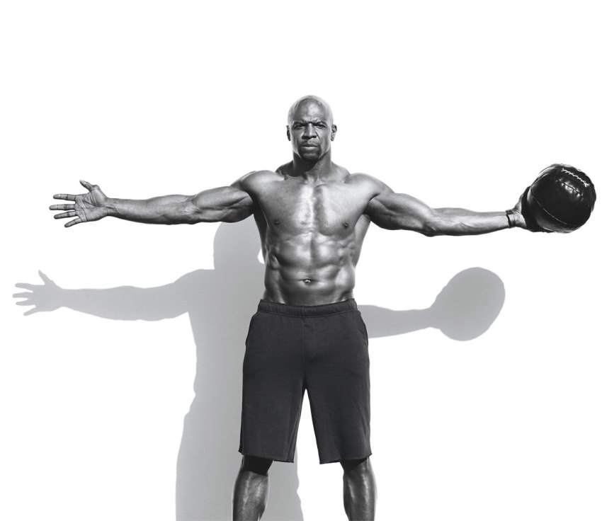Terry Crews having his hands widespread while looking directly in the camera, showing his ripped physique