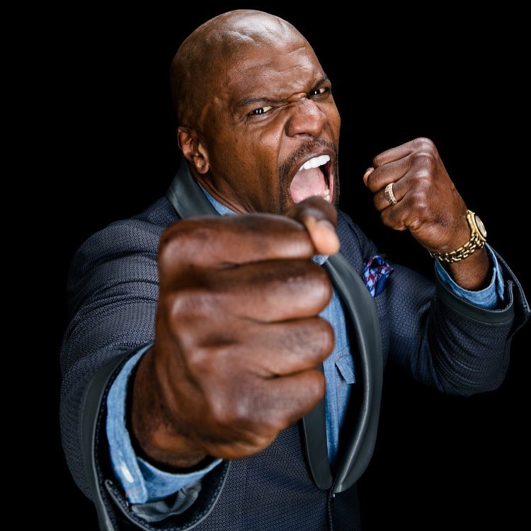 Terry Crews in a suit with an angry expression on his face pointing his fists and yelling at the camera