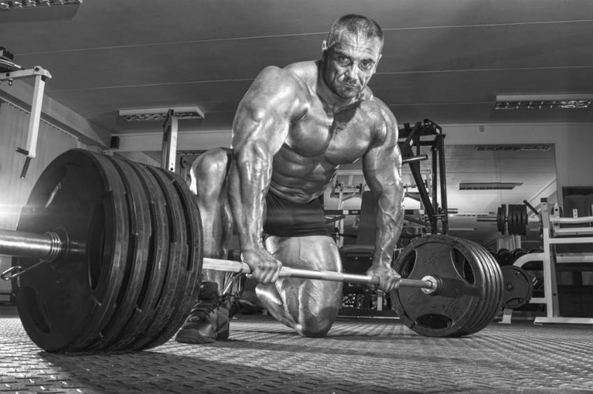 tomas kaspar kneeling in front of barbell