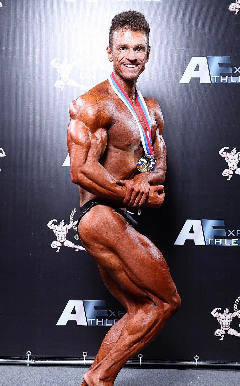 Vlad Lapshin backstage smiling while being in a side chest pose with a gold medal around his neck