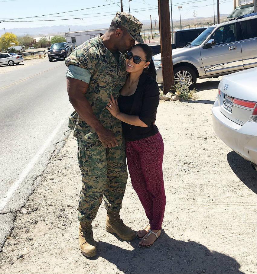 xavisus gayden hugging his wife with his bicep showing