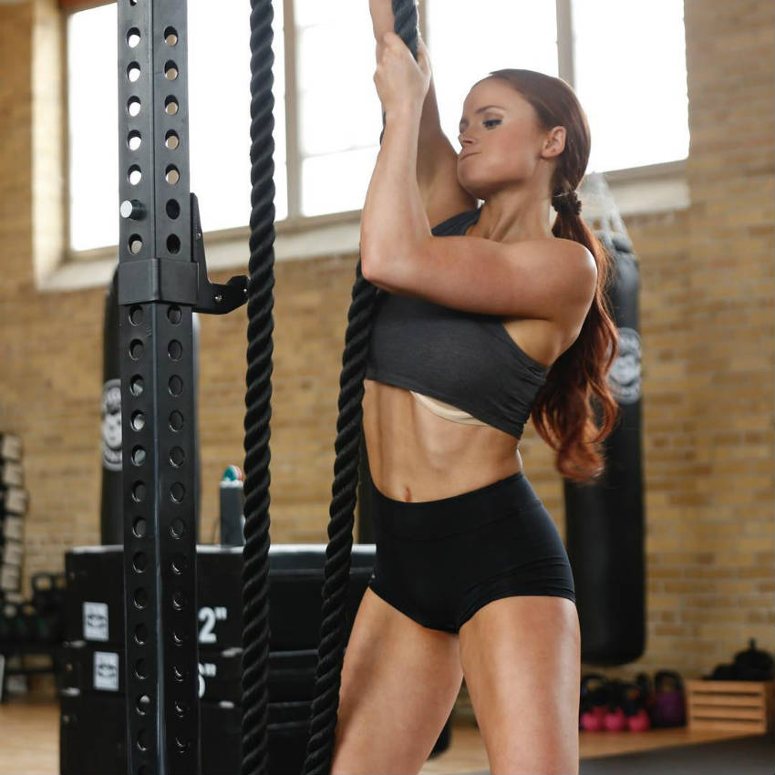 Abby Pollock pulling a rope and showing her strong triceps toned abs and quads