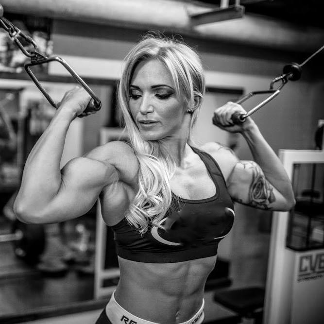 Black and white picture of Alina Pettke doing cable biceps curls while showing her lean abs