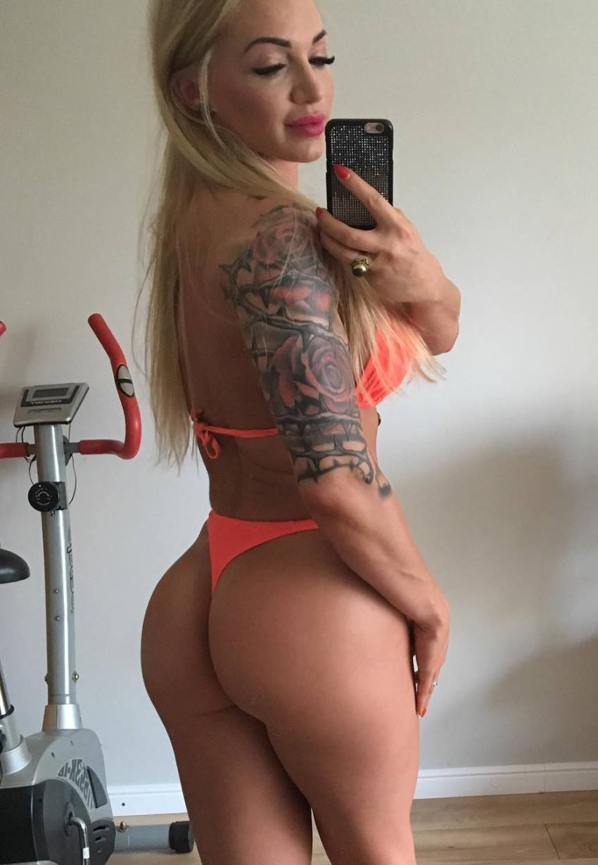 Alina Pettke taking a selfie besides a cardio machine, showing her tattoed arms and stunning glutes