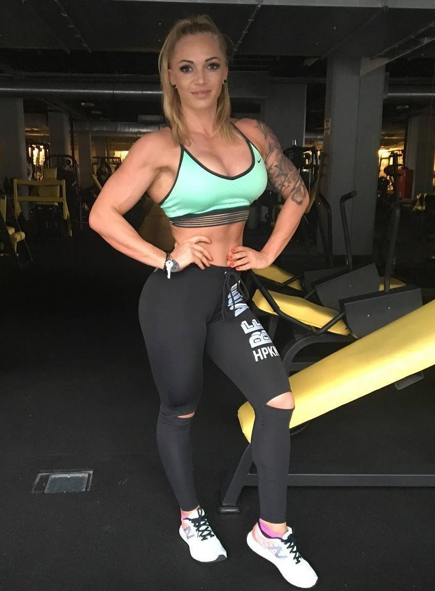 Alina Pettke standing in a gym, posing for a photo in sportswear