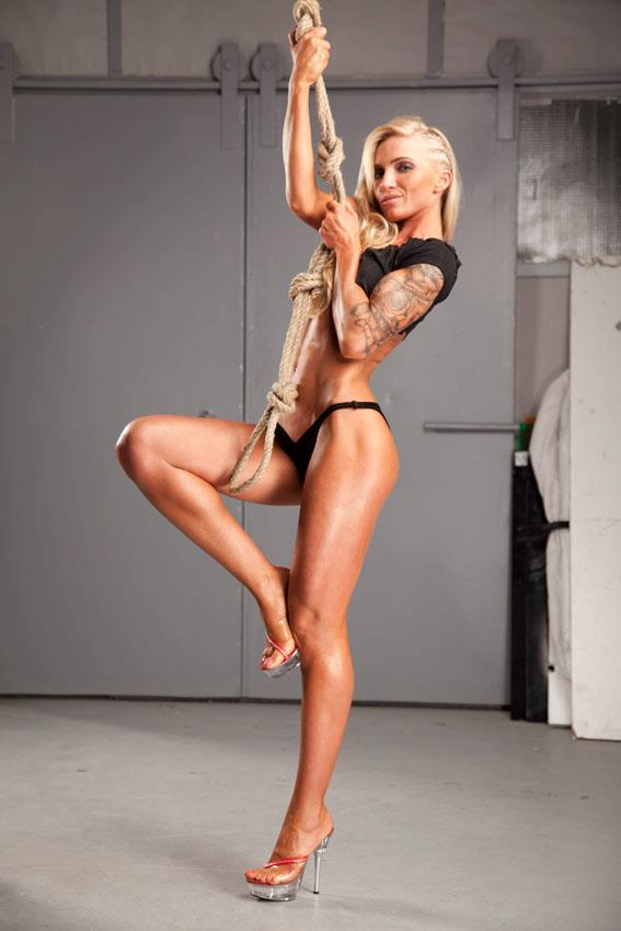 Alina Pettke holding a rope in her arms as she poses for a photo, showing her fit legs and arms from the side