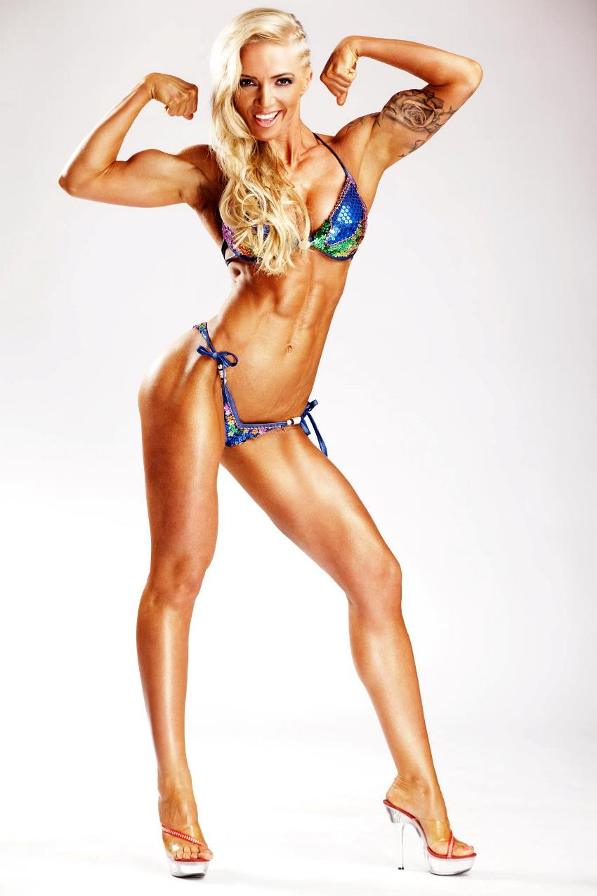 Alina Pettke doing a front double biceps pose with a smile on her face, while wearing a bikini