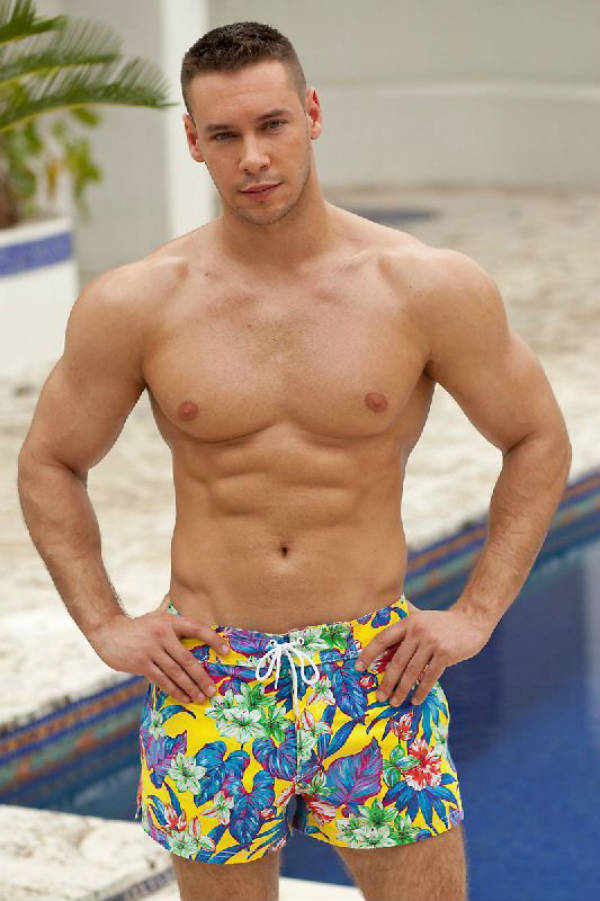 Anton Antipov standing in swimming shorts, showing his ripped abs and well-built chest