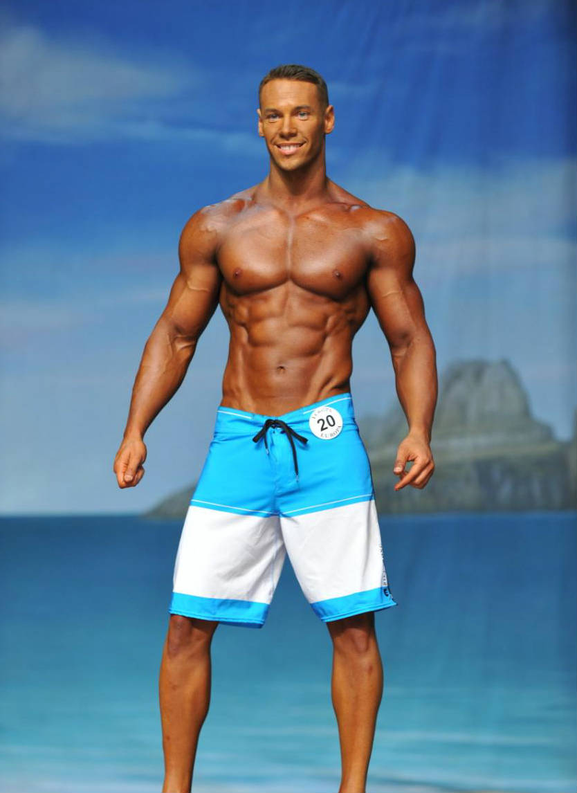 Anton Antipov standing n board shorts at a competition, showign off his reipepd abs, toned obliques and large chest and delts