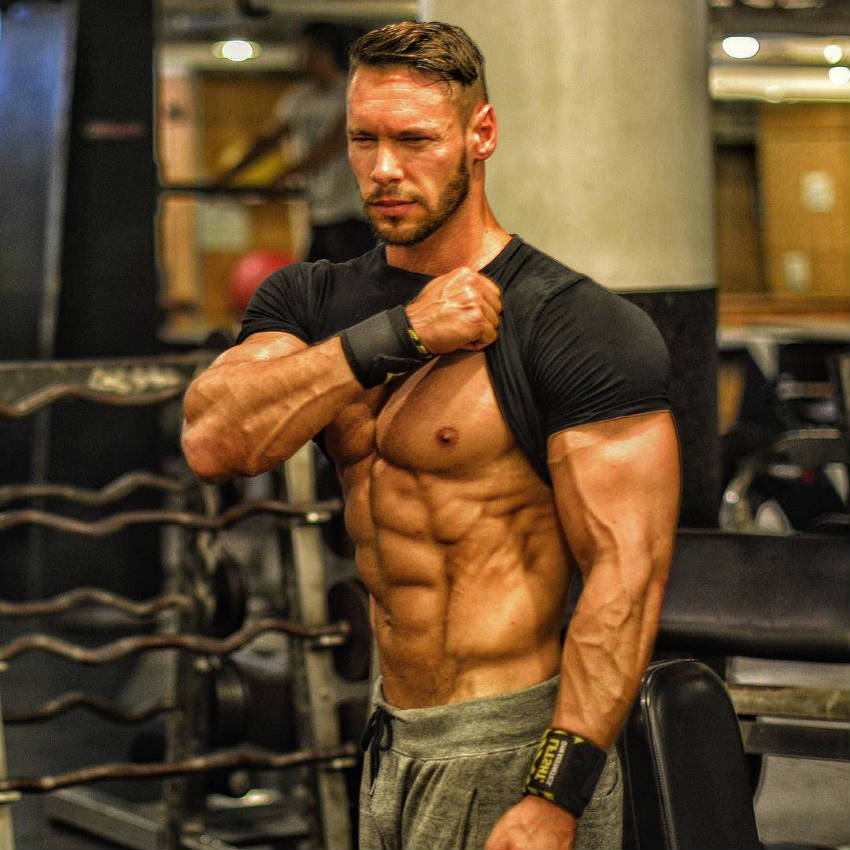 Anton Antipov lifts his shirt and shows his ripped abs and toned oblique
