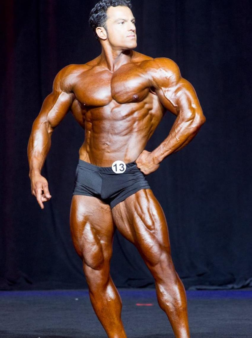 Arash Rahbar confidently posing on the stage in black trunks, showing his classic golden era physique to the judges