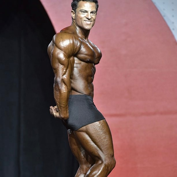 Arash Rahbar making waves on the Classic Olympia stage with his side triceps pose, displaying immaculate conditioning