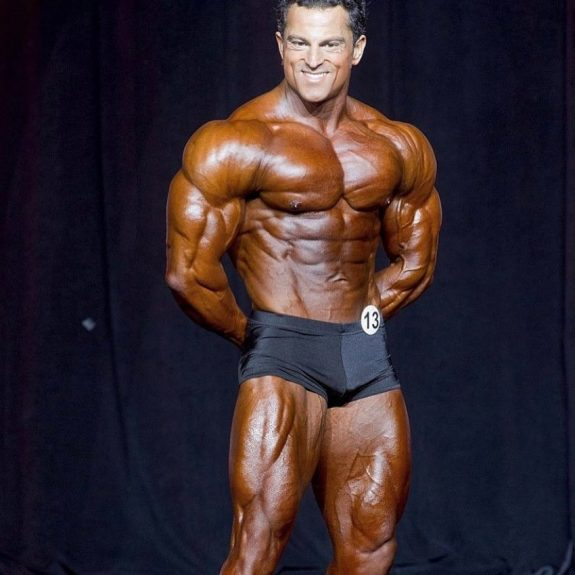 Arash Rahbar showing a variation of his most muscular pose to the judges on the stage, smiling at them, and being confident in his impressive physique