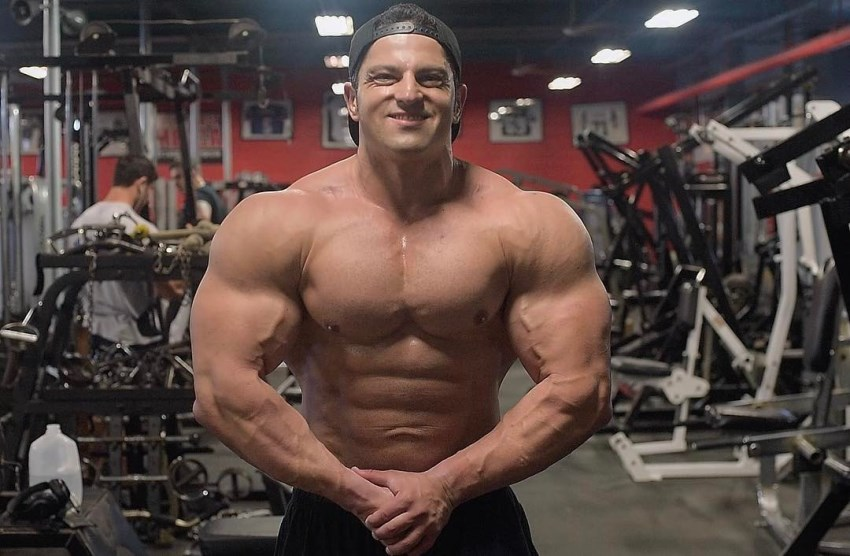 Arash Rahbar in the offseason, posing in the gym, showing his massive, yet aesthetic physique