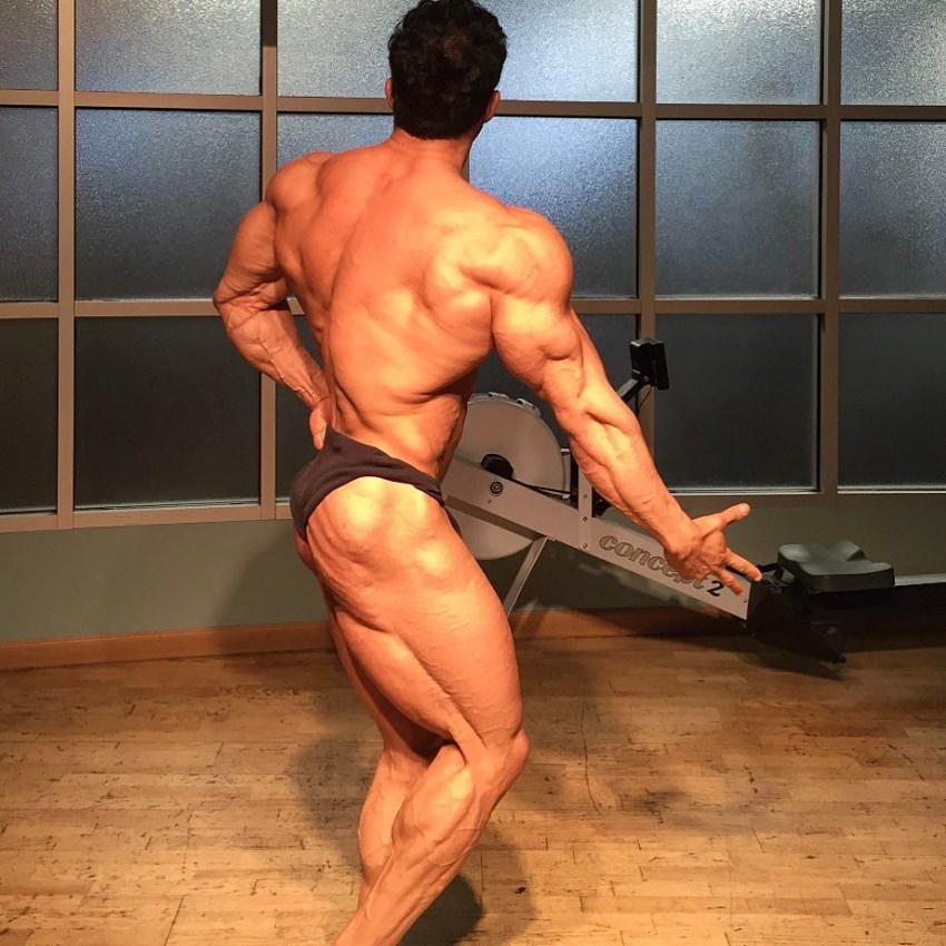 Arash Rahbar practicing posing in a room, his back and legs looking incredible from the side