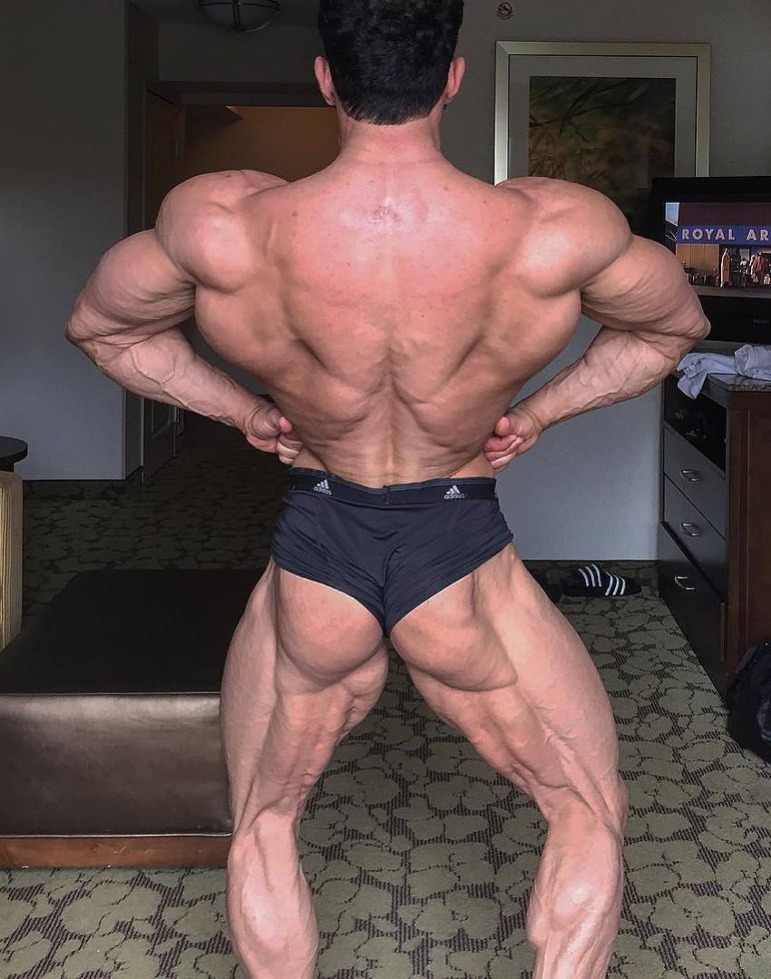 Arash Rahbar practicing rear lat spread pose at his home, looking incredibly conditioned