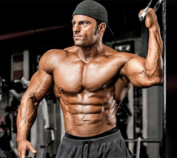 Arash Rahbar doing a photoshoot in the gym, holding onto a cable, and showing his ripped and muscular body
