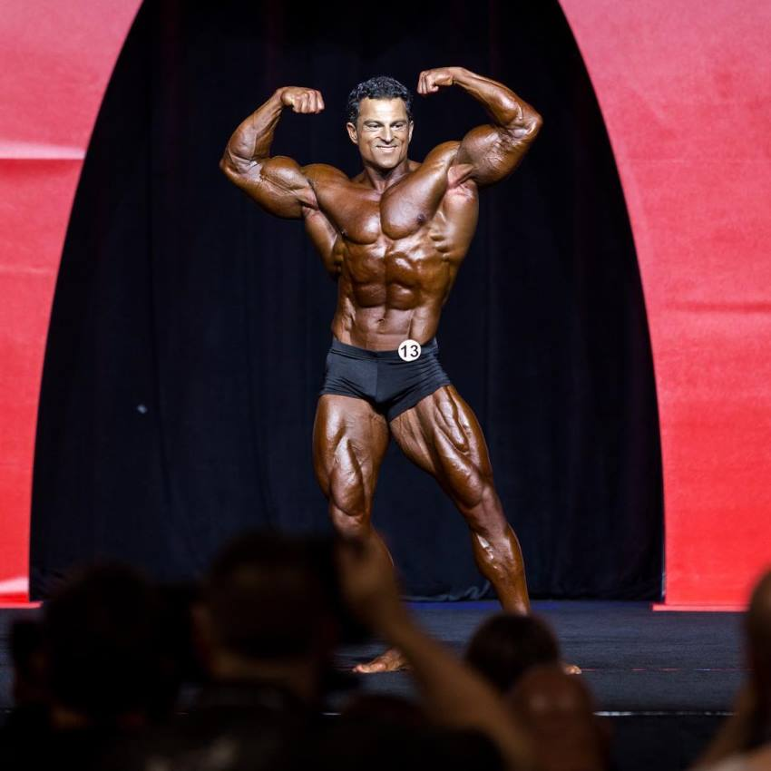Arash Rahbar doing a double biceps flex pose on the olympia stage, smiling at the photographers, judges, and fans who are cheering him up in the background