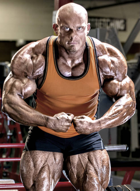 Ben Pakulski showing off his large and toned quads, well-built arms and large chest