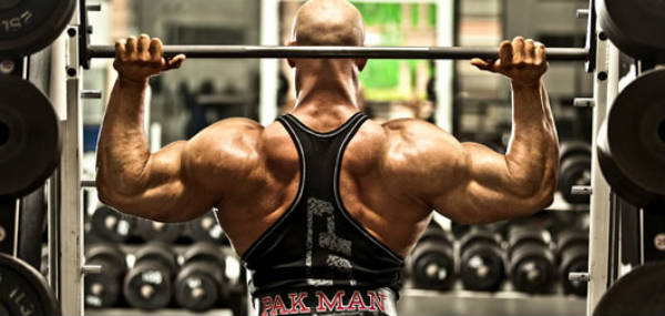 Ben Pakulski completing an overhead press with his large delts, back and 'pak man' weightlifting belt showing