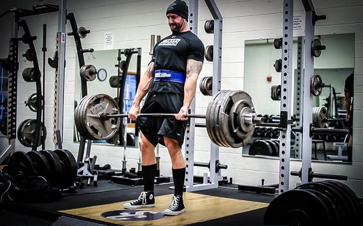 Brandon Campbell completing a deadlift in a powerlifting gym