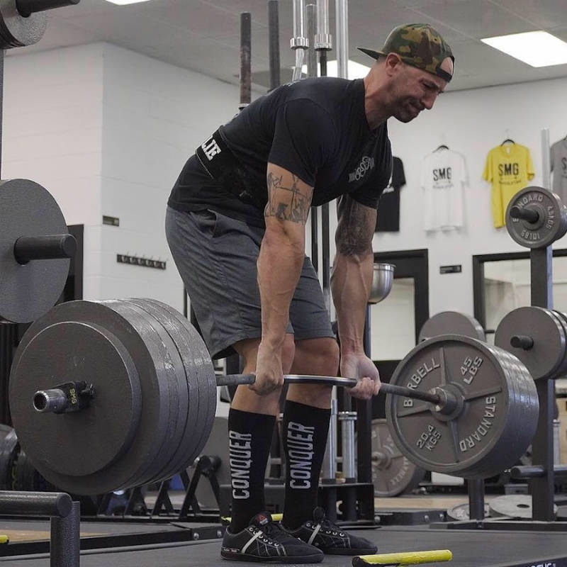 Brandon Campbell completing a deadlift and showing his large arms