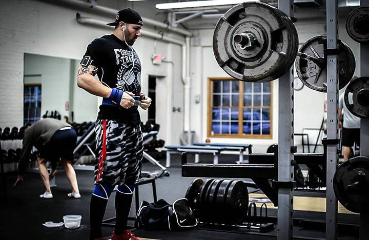 Brandon Campbell standing in the powerlifting gym, showing his large arms and legs