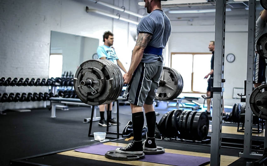 Brandon Campbell completing a deadlift and showing his large trices